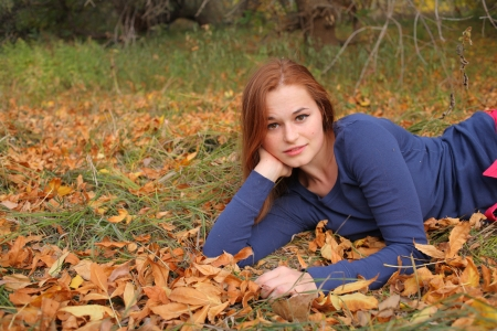 Young woman lying in the fall leaves photo