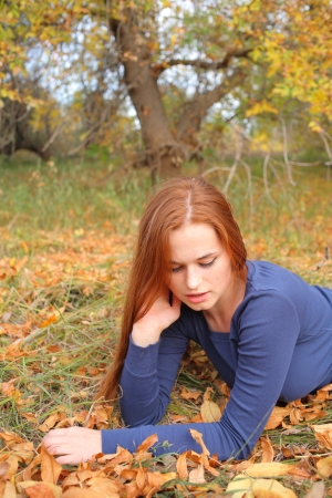 Redhead girl sitting at outdoor in autumn time  photo
