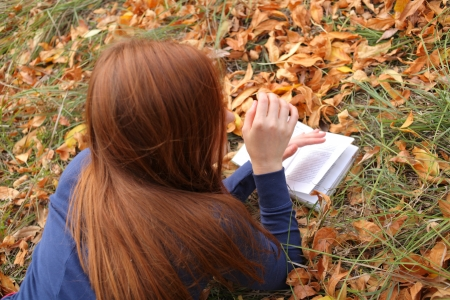 Redhead woman lies on green grass and reads book, Happy smiling beautiful young university student studying lying down in grass. photo