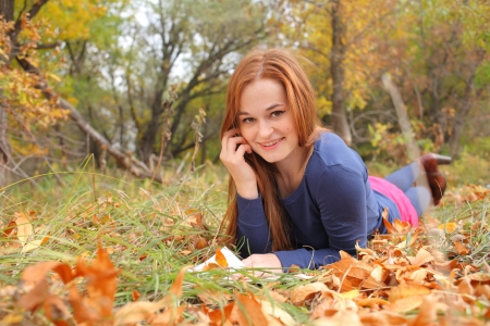 hands behind head: Attractive redhead in autumn leaves