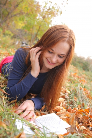 Young Woman  Leaning Book outdoors in autumn park Stock Photo - 15785828