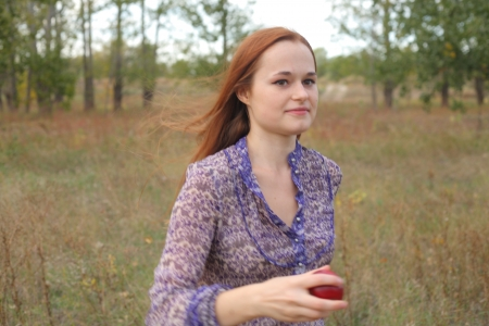 Beautiful young redhead in a autumn meadow with red apple photo