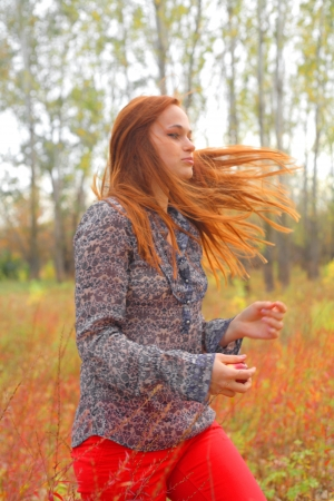 Beautiful young redhead in a autumn meadow wind blowing photo