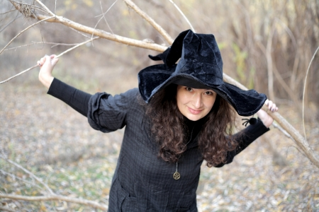 Sexy  girl in witch costume for Halloween in a forest photo