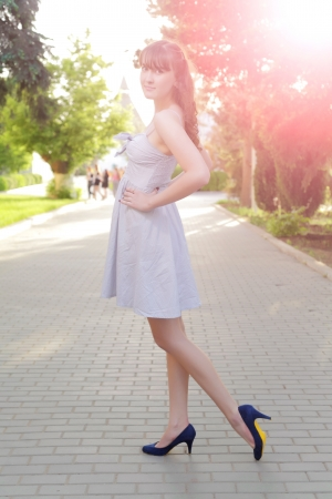 Full length portrait of an alluring young blond woman in dress outdoor backlit photo
