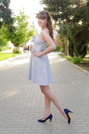 Full length portrait of an alluring young blond woman in dress outdoor photo