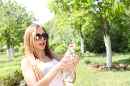 Portrait of a beautiful sexy woman outdoors playing with water in bottle having fun - waterdrops flying