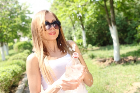 sexiness: Portrait of a beautiful sexy woman outdoors playing with water in bottle having fun