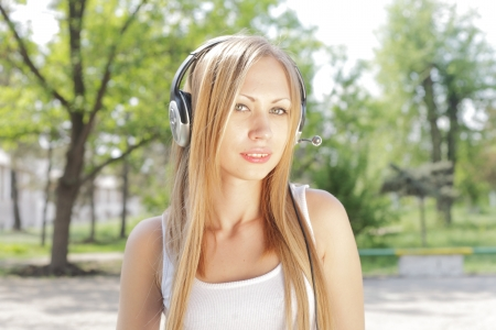 beautiful girl with blond hair, listening to music on headphones photo
