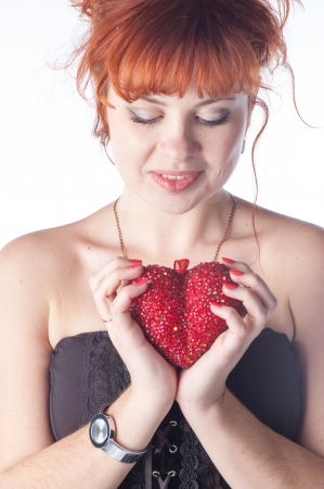Portrait of beautiful redhead caucasian girl with heart in hand. Stock Photo - 17395838