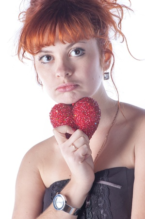 Portrait of beautiful redhead caucasian girl with heart in hand. photo