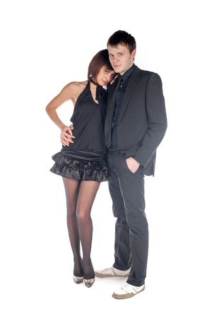 Young serious couple  Woman embraces man  Woman in a black dress photo