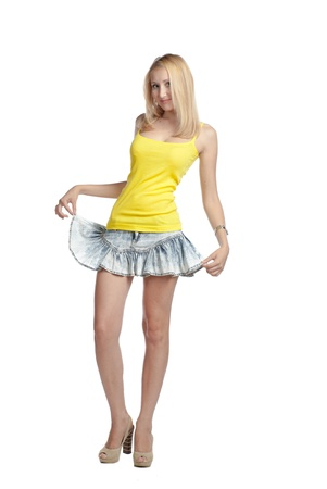 beautiful blond woman in yellow tank top and jeans skirt full body studio on white background photo
