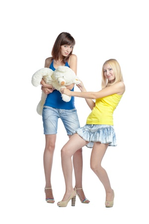Two young women with different colors of the hairs with teddy bear isolated on white background in different emotional states Stock Photo - 17638151