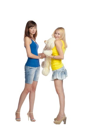 Two girls blonde and brunette with teddy bear isolated on white photo
