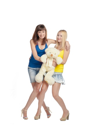 Two girlswith teddy bear isolated on white photo