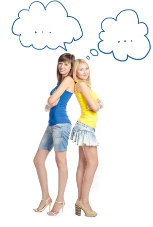Two attractive girl friends thinking - blond and brunette on white background. Yellow and blue tank top and jeans. photo