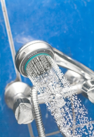 A shower head is spraying water on the blue background in bath room  Spa health concept Stock Photo - 17843757