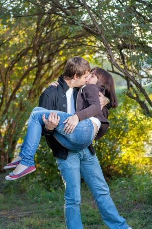 lovers park: Happy young couple. Holding women on the hands and fav fun a lot of positive emotions