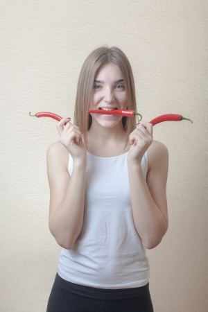 Pretty blond woman head and shoulders shot holding in hands red spicy pepper and biting another one on beige background. Healthy nutrition diet concept photo
