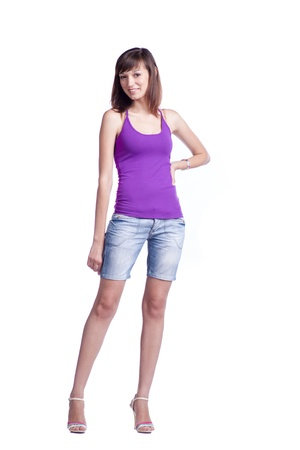 charming brunette women 20-25 years old standing in studio isolated on the white background. Violet tank top, jeans shorts photo