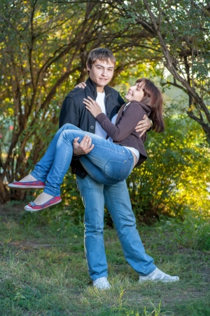 Happy young couple. Holding women on the hands and fav fun a lot of positive emotions photo