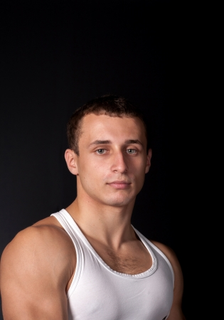 a male in white tank top with strong muscles on the black background photo
