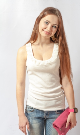 Portrait of a pretty, smiling blonde in jeans on white  20-24 years old young women in studio front view photo
