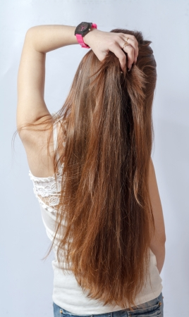 Girl with long fair hair from back, on white background