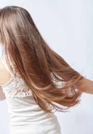 long shots: biondi capelli al vento vista posteriore su sfondo grigio Archivio Fotografico