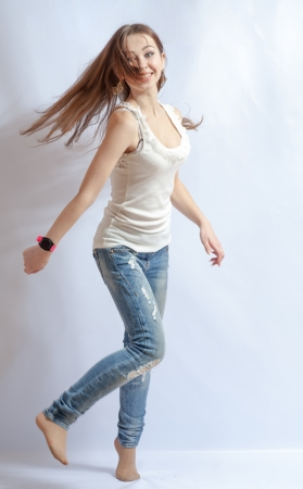 Young female dancing, fluttering on the wind hair, over white background photo