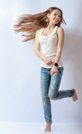 no heels: Young female dancing, fluttering on the wind hair, over white background