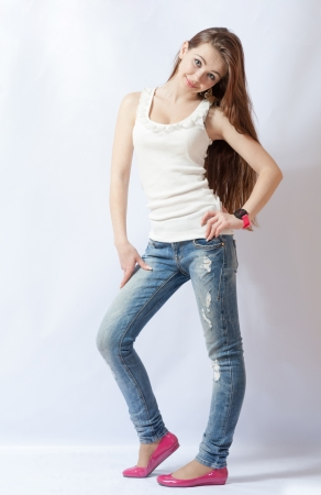 Full length portrait of a caucasian blond woman in blue jeans and pink shoes on gray background photo