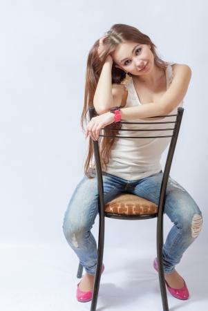 mujeres sentadas: Una joven mujer rubia descansando en una silla en una blusa blanca y pantalones vaqueros azules para el fondo blanco en el estudio