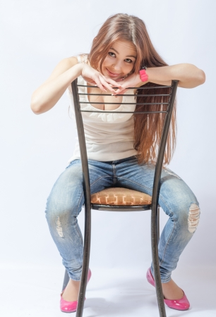 no shirt: A young blond woman resting on a chair in a white blouse and blue jeans for white background in the studio