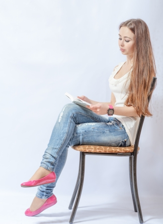 no heels: Closeup portrait of a young smiling woman sitting on a chair in jeans reading a book