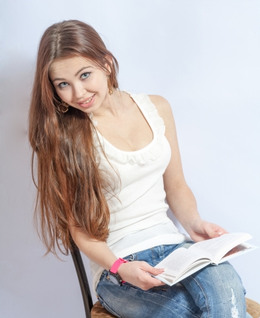 Closeup portrait of a young smiling woman sitting on a chair in jeans reading a book photo