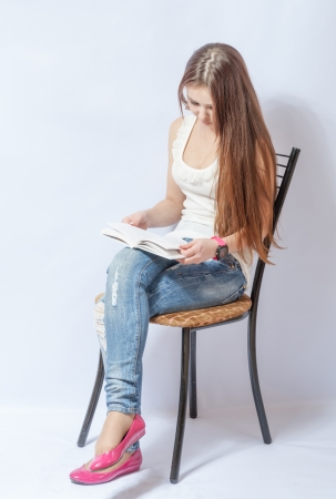 full lips: Closeup portrait of a young smiling woman sitting on a chair in jeans reading a book