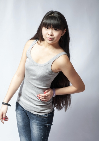 Front  view of standing young beautiful Asian woman in tank top and jeans torso shot  Teen watching  Front view  Backside view of person  Shot over white background  photo