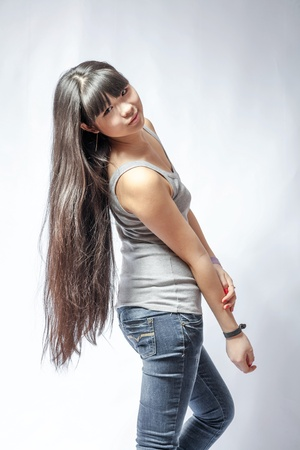 back view of standing young beautiful Asian woman in tank top and jeans torso shot  Teen watching  Rear view  Backside view of person  Shot over white background  photo