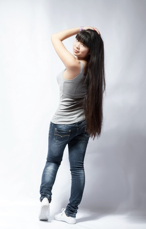 back view of standing young beautiful Asian woman in tank top and jeans full body   Teen watching  Rear view  Backside view of person  Shot over white background  photo