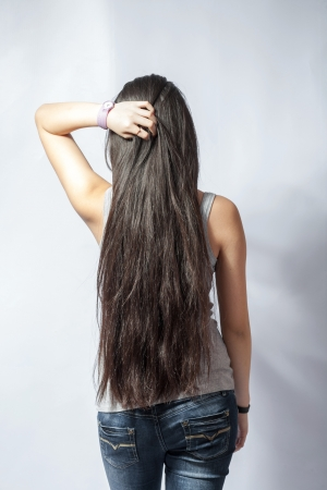 Back of young woman with long hairs, dressed in jeans  Isolated on white photo