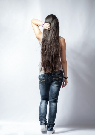 back straight: Back of young woman with long hairs, dressed in jeans  Isolated on white
