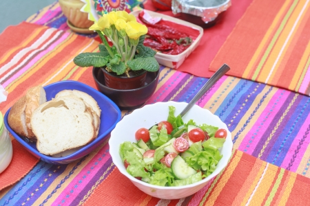 A green salad in a stylish white bowl  With rocket leaves cherry tomatoes spanish onions and capsicum  Flowers   red pepper and bread on the table too photo