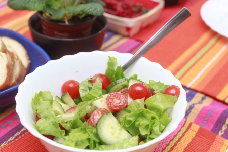 A green salad in a stylish white bowl  With rocket leaves cherry tomatoes spanish onions and capsicum  photo