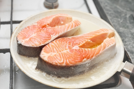 Preparing healthy salmon lunch in a frying pan photo
