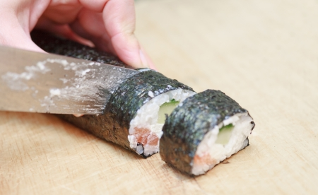 this is a a close-up of hands and a knife cutting sushi  photo