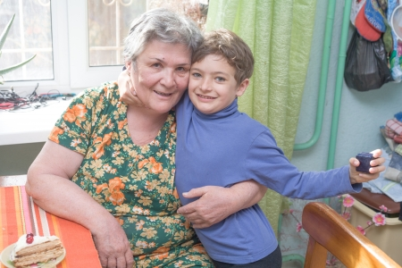 Portrait of a happy little boy sitting on his grandmothers lap