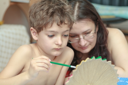 Mother and son painting indoors photo