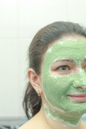 Young woman applying green algae facial mask  photo